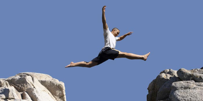Guy jumps from one rock to another in a big leap