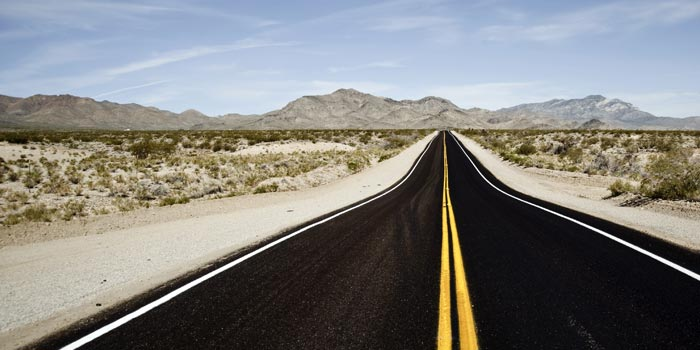 A road in the desert stretches out toward the horizon and mountains