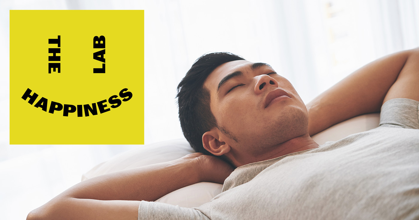 The Happiness Lab logo floats over top of a relaxing person.